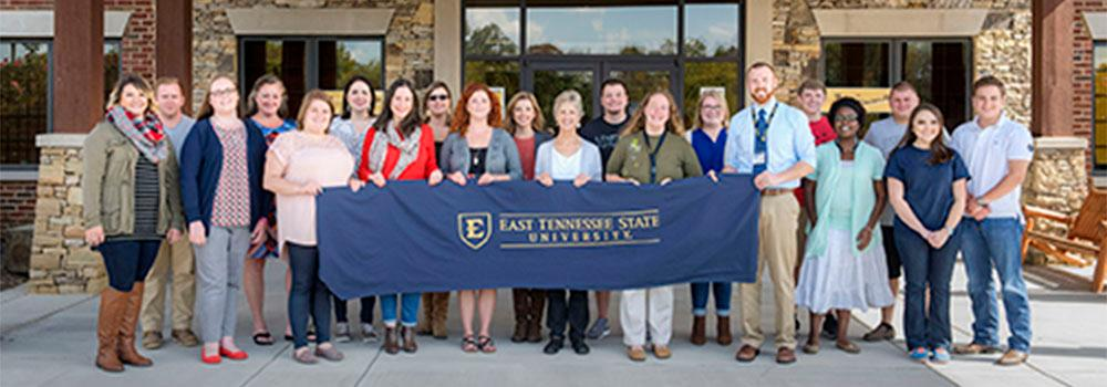 A crowd of people outside our Sevierville campus holding an ETSU banner.