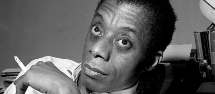 James Baldwin holding a cigarette between his fingers