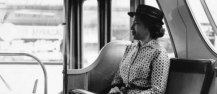 Rosa Parks on a bus looking out a window
