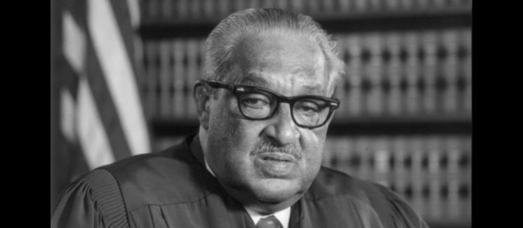 Thurgood Marshall in front of a bookcase