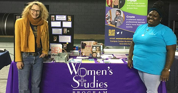 two women stand in front of a table with promotional materials