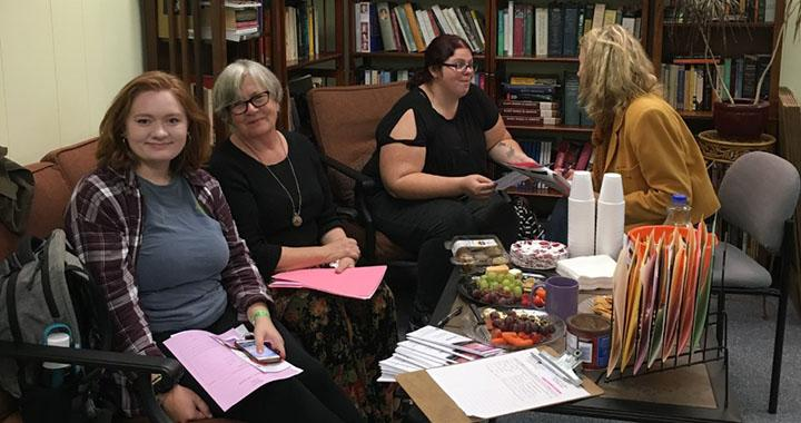 four women sit and talk