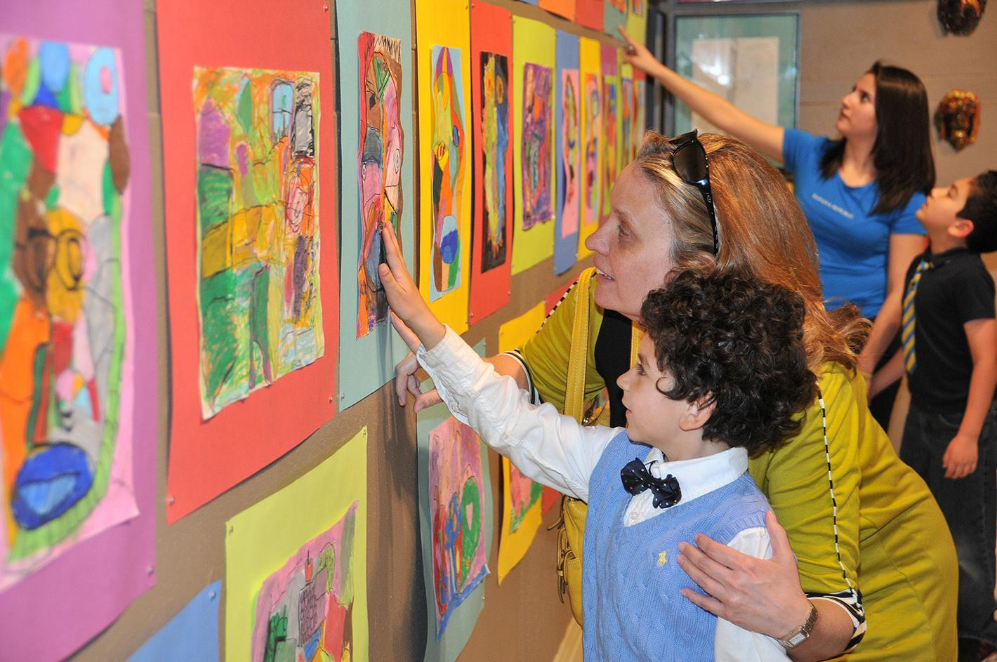 A young artist views his work in the exhibition Exuberance! Kids Make Art about Art curated by Sammie Nicely. The exhibition was in the Reece Museum in 2015.