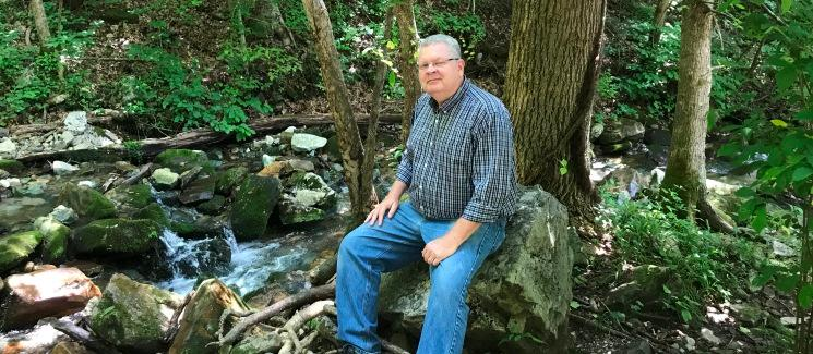 Dr. Holmes sitting on a rock in front of trees and a creek.