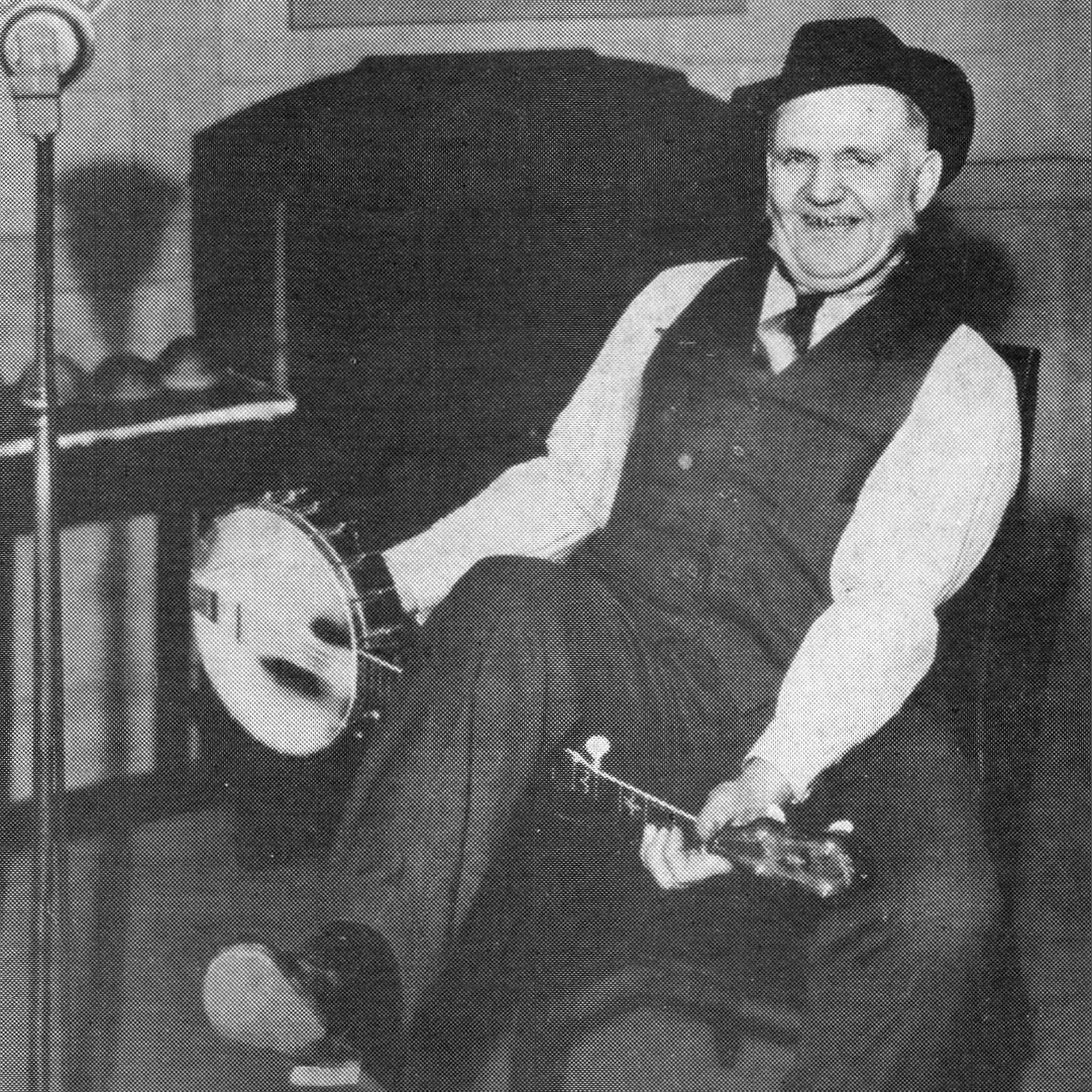 Uncle Dave Macon with a banjo under his leg