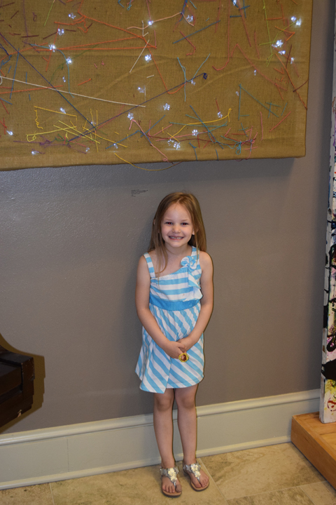 young girl poses with artwork