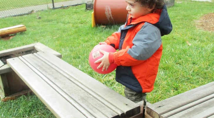 boy plays with ball outside