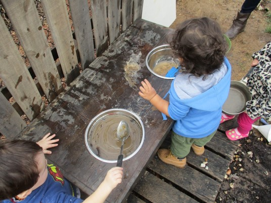 "children ""cooking"" with sand and water"