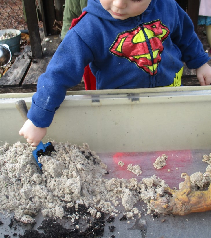 child scooping sand and soil