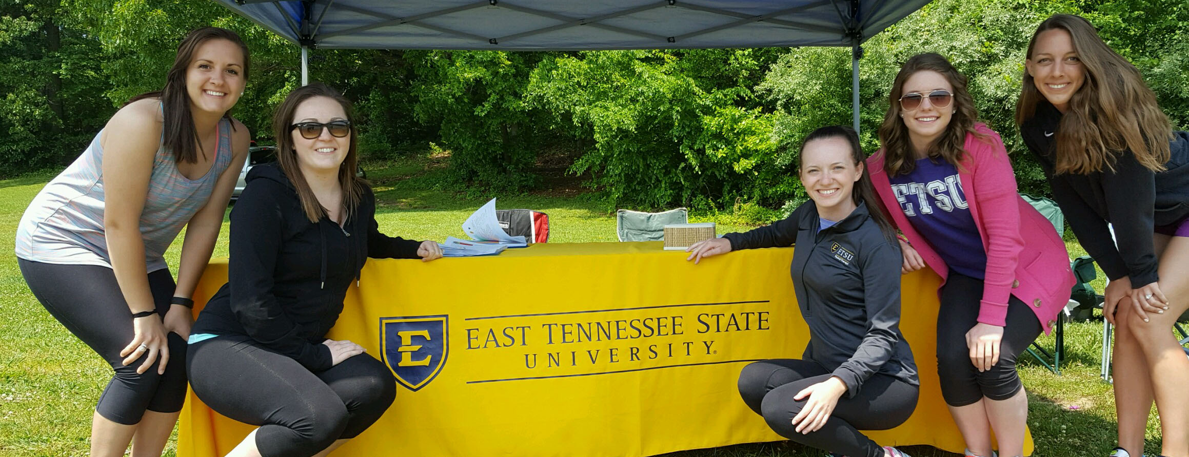 students posing at an ETSU booth