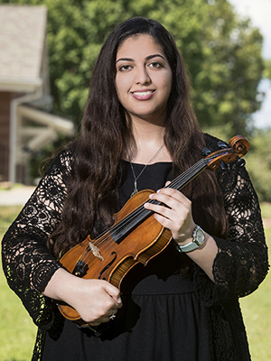 Abeer Chaudhary, pictured in front of the Ada Earnest Honors House holding her violin.