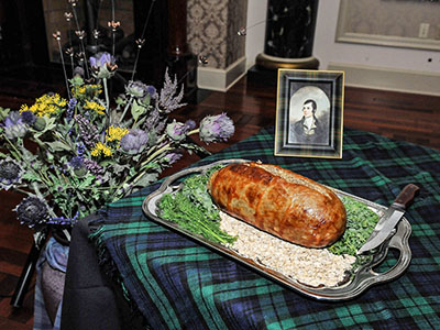 A still photo featuring the haggis, a portrait of Robert Burns, and bouquet of dried thistle.